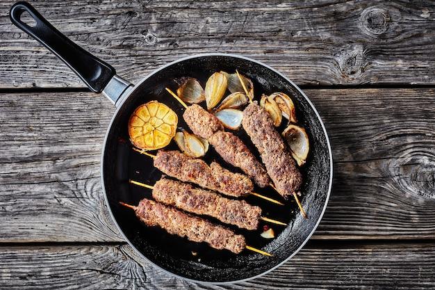 Keto dieetvoeding: kofta kebab van lamsgehakt gebakken in de oven aan spiesjes met kruiden op een koekenpan