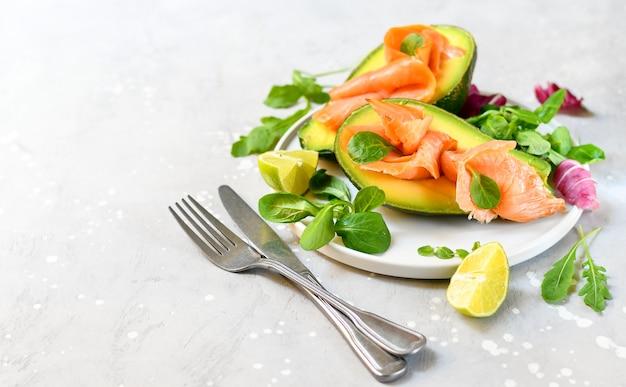 Keto dieetvoeding zalm en avocadosalade met rucola en limoen. ketogeen voedsel