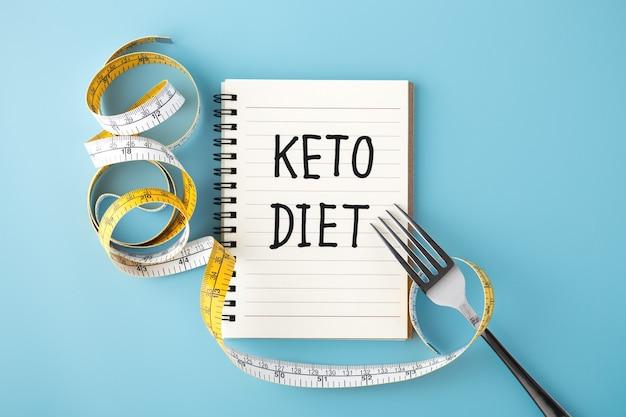 Keto-dieetwoord op notitieboekje met meetlint en vork