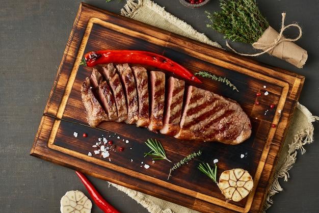 Keto ketogeen dieet biefstuk, gegrilde gebakken striploin op snijplank op donkerbruine tafel