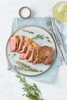 Keto ketogeen dieet biefstuk, striploin op grijze plaat op wit.
