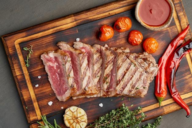 Keto ketogeen dieet gegrilde gebakken biefstuk, striploin op snijplank op donkerbruine tafel