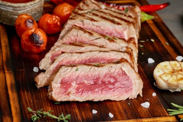 Keto ketogeen dieet geroosterde gebakken rundvlees steak, striploin op snijplank, zijaanzicht, close-up Premium Foto