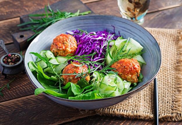 Keto / ketogeen voedsel. kippengehaktballetjes en salade op houten lijst. avondeten. boeddha schaal.