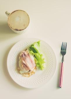 Keto-ontbijt met spek, gebakken eieren, groene salade en kopje koffie met melk op witte houten tafel. gezonde vetten concept
