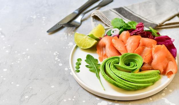 Keto voedsel zalm en avocado salade met rucola en limoen. ketogeen voedsel