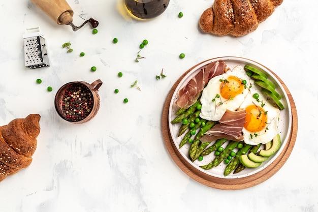 Ketogeen dieet gezond ontbijt asperges met prosciutto, avocado en gebakken eieren