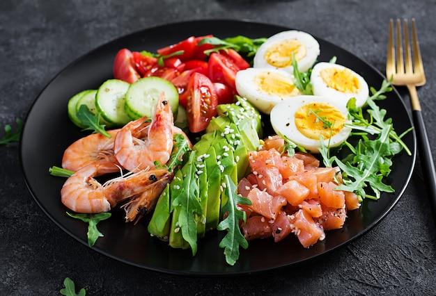 Ketogeen dieet ontbijt. zoute zalmsalade met gekookte garnalen, gamba's, tomaten, komkommers, rucola, eieren en avocado. keto, paleo-lunch.