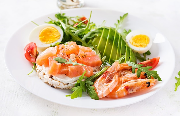 Ketogeen dieet ontbijt. zoute zalmsalade met gekookte garnalen, gamba's, tomaten, rucola, eieren en avocado. keto, paleo-lunch.