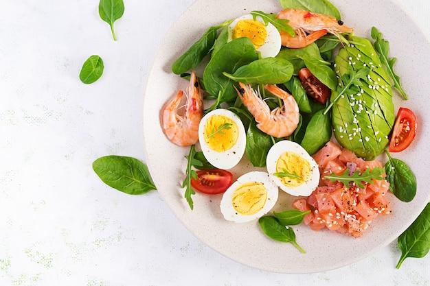 Ketogeen dieetontbijt. zoute zalmsalade met gekookte garnalen, garnalen, tomaten, spinazie, eieren en avocado.