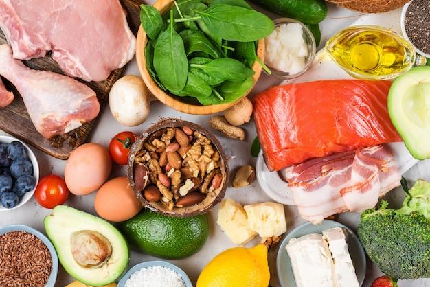 Ketogeen dieetvoeding. gezonde koolhydraatarme producten. keto dieet concept. groenten, vis, vlees, noten, zaden, bessen, kaas Premium Foto