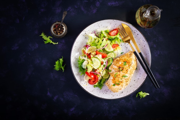 Ketogeen, keto-eten. gebakken kipfilet en verse groentesalade van tomaten, komkommers en sla. kippenvlees met salade. gezond eten. bovenaanzicht, plat leggen, kopie ruimte