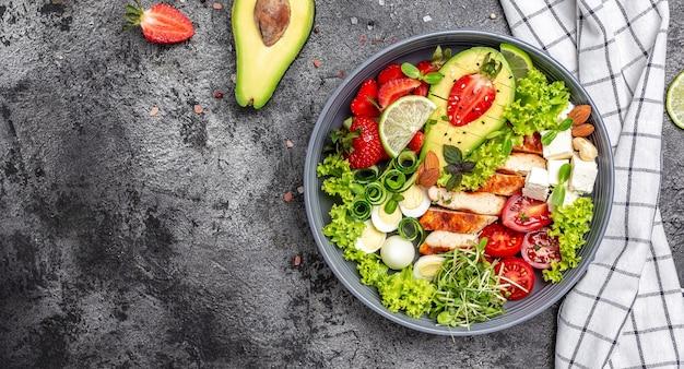 Ketogeen, keto of paleodieet lunchkom met gegrilde kip en avocado, fetakaas, kwarteleitjes, aardbeien, noten en sla. trends in gezond eten. bovenaanzicht.