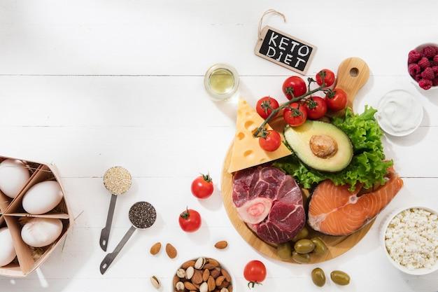 Ketogeen koolhydraatarm dieet - voedselselectie op wit oppervlak. vlees, vis en groenten. kopieerruimte.