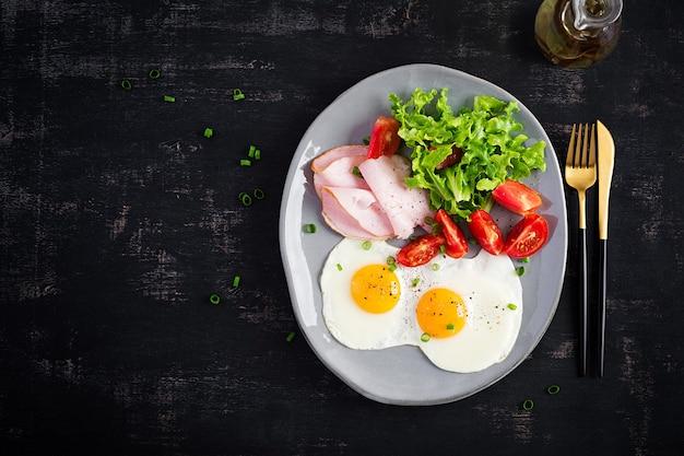 Ketogeen / paleodieet. gebakken eieren, ham en frisse salade. keto-ontbijt. brunch. bovenaanzicht, boven het hoofd
