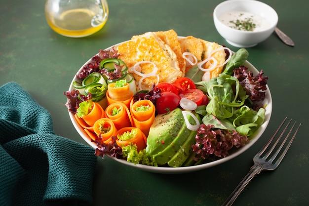 Ketogene paleodieet lunchkom. halloumi kaas, avocado wortel komkommer sla