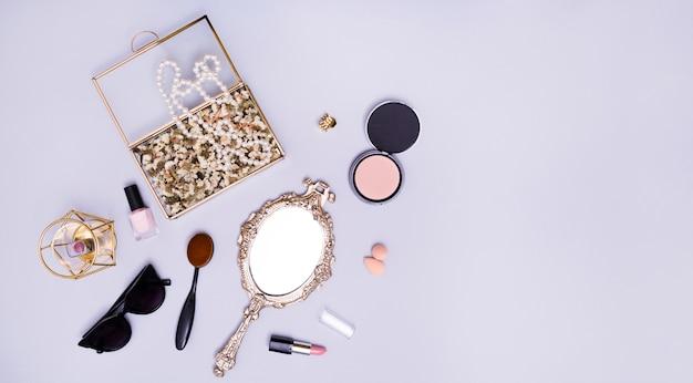 Ketting en bloemen in de doos; lippenstift; blender; zonnebril; ovale kam; compact poeder; lippenstift en handspiegel op paarse achtergrond