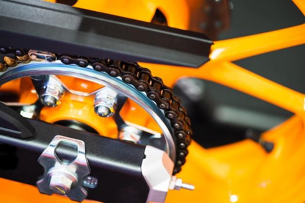 Ketting en tandwiel van nieuwe gele motocycle dichte omhooggaand