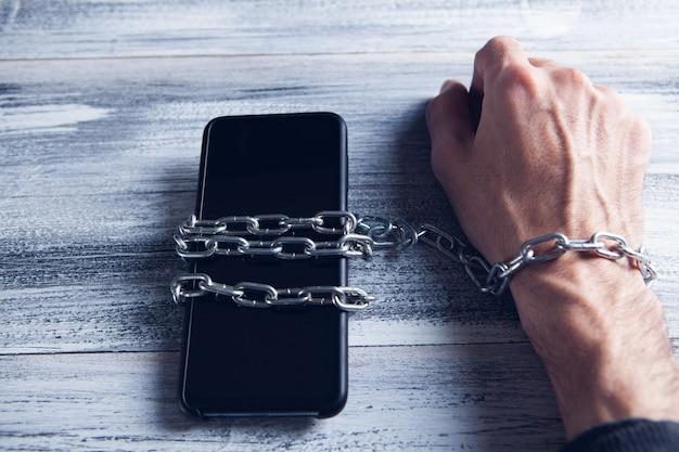Ketting en telefoon in de hand. telefoon verslaving concept