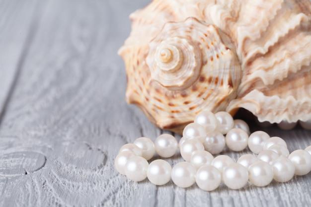 Ketting gemaakt met parels en zeeschelp op wit hout
