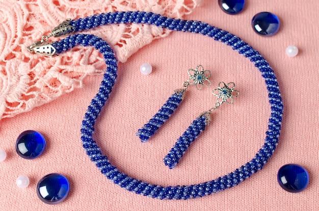 Ketting gemaakt van kleine kralen bezet met handgemaakte oorbellen. blauwe kralenversiering