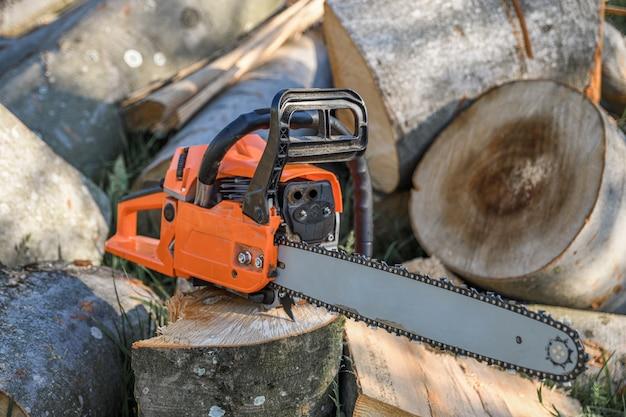 Kettingzaag die op een hoop brandhout in de tuin staat op een achtergrond van brandhout en bomen die met een kettingzaag zijn doorgesneden.