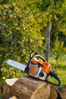 Kettingzaag die op een hoop brandhout in de tuin staat