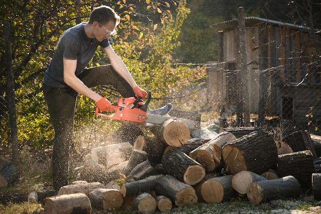 Kettingzaag die staat op een hoop brandhout in de tuin op een prachtig groen gras en bos.