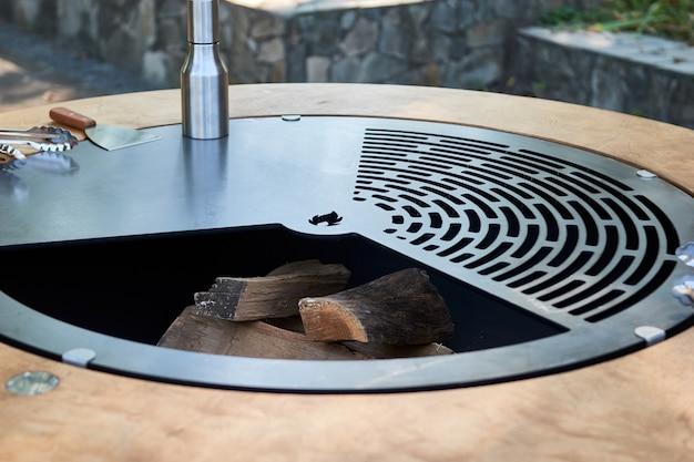 Kettle grill pit met gietijzeren rooster met vlammen. ronde tafel-kookplaat. warme bbq op achtertuin