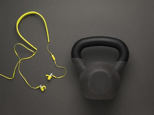 Kettlebell en gele koptelefoon op een gele achtergrond. sportieve levensstijl. kleuren 2021.