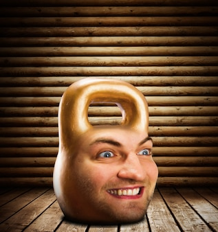 Kettlebell met mannelijk gezicht in houten kamer