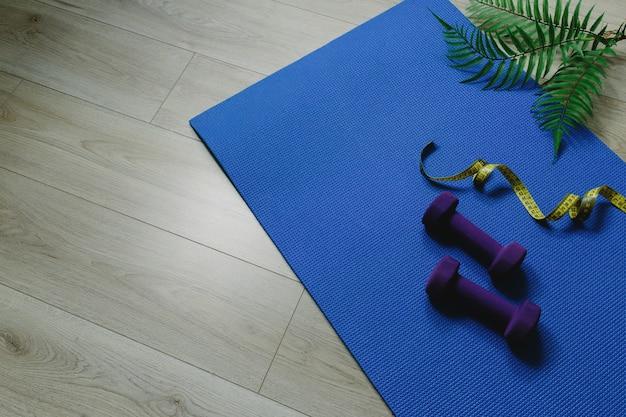 Kettlebells of gewichten, blauwe pad, houten laminaat, varenbladen, meetlint