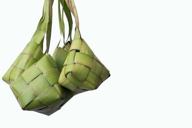Ketupat (rijstbol) is een traditioneel gerecht van indonesië tijdens eid mubarak dat over wit oppervlak wordt geïsoleerd