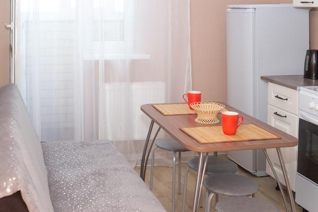 Keuken interieur. houten tafel in het midden van de kamer met keukengerei. huishoudelijke apparaten en recreatiegebieden.