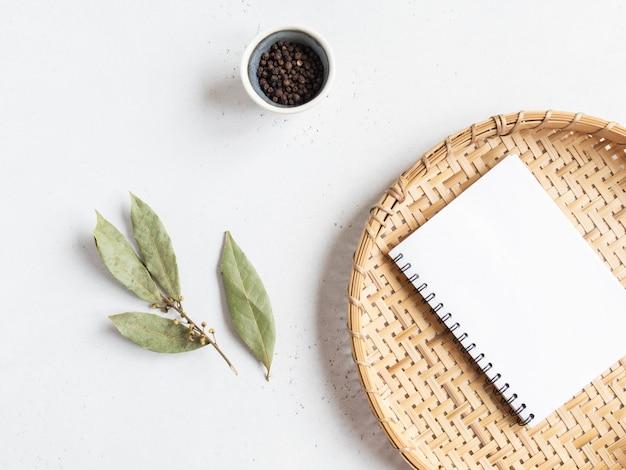 Keuken notitieblok mock up voor culinaire tekst, rieten dienblad en kruiden