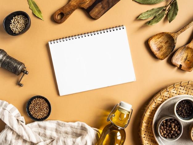 Keuken plat lag met open kladblok voor culinaire tekst en kleine schaaltjes diverse droge kruiden, houten keukengerei, olijfolie in glazen fles