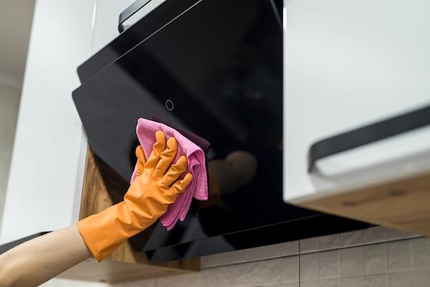 Keuken schoonmaken. vrouwelijke handwas afzuigkap met spons. huiswerk