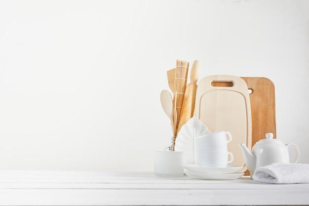 Keukenachtergrond voor mockup met lepel, theepot, koppen, deegrol, kommen op houten lijst