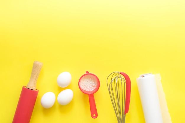 Keukenapparaten om te bakken en ingrediënten op een heldere gele achtergrond. bovenaanzicht, kopieer ruimte. plaats voor tekst.