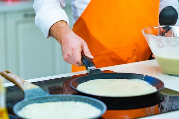 Keukenbereiding: de chef-kok frituurt verse pannenkoeken in twee pannen