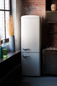 Keukenbinnenland in donkere geweven kleuren met witte moderne retro koelkast, rustieke bakstenen muur