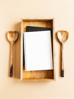 Keukenblok of kookboek mock up voor culinaire tekst op houten dienblad en houten lepels
