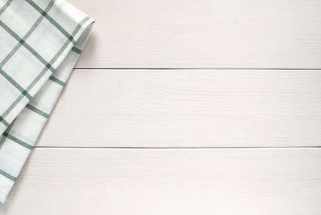 Keukendoek aan zijkant van witte houten tafel
