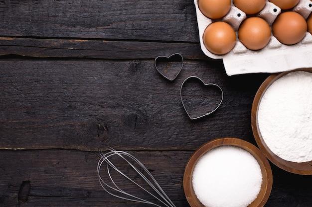 Keukengereedschap, bloem en suiker op hout