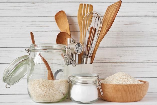 Keukengereedschap en glazen pot met rijst