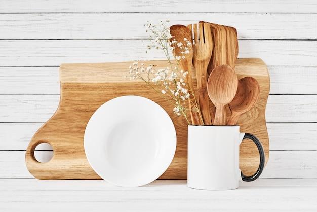 Keukengereedschap en snijplank op witte tafel