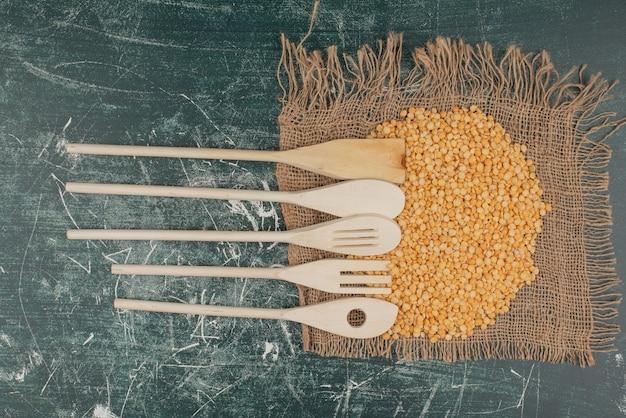 Keukengereedschap en tarwe op jute op marmeren oppervlak
