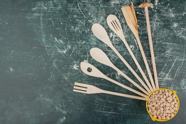 Keukengereedschap met gele emmer met noten op marmeren achtergrond. hoge kwaliteit foto
