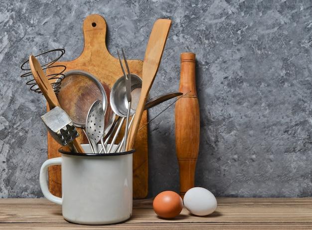 Keukengereedschap om op een houten lijst op de achtergrond van een concrete muur te koken de ruimte van het exemplaar. lepel, vorken, houten spatel, deegroller, eieren.