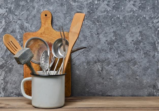 Keukengereedschap om op een houten lijst op de achtergrond van een concrete muur te koken de ruimte van het exemplaar. lepels, vorken, houten spatel.
